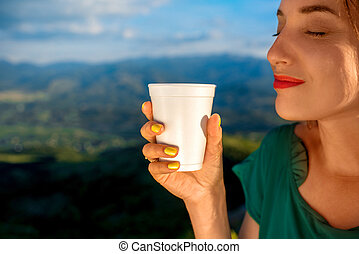 Woman enjoying coffee to go - Young woman holding white...