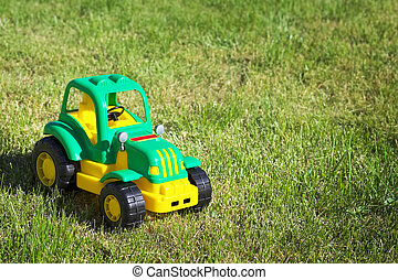 Toy green-yellow tractor on the green grass.