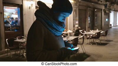 Woman with cell phone outdoor at night - Steadicam shot of a...