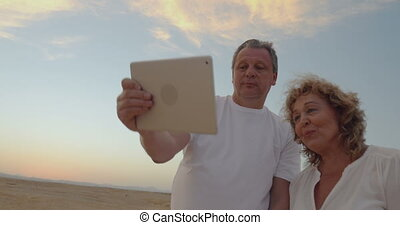Senior couple using touch pad outdoor on vacation - Happy...