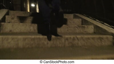 Woman running in dark alleyway at night - Steadicam shot of...