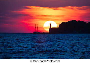 Epic sunset view with lighthouse and saiboat in Zadar,...