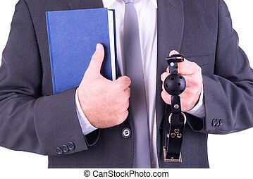 Erotic novel concept - Businessman holding ball gag and book...