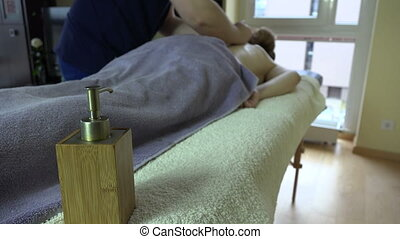 massage oil woman back - Massage oil and therapist is...