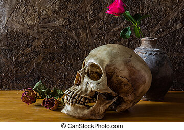 Still life with human skull with red rose in the old vase on...