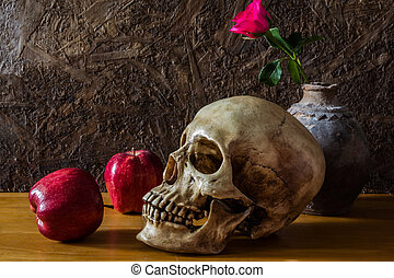 Still life with human skull with red rose in the old vase...