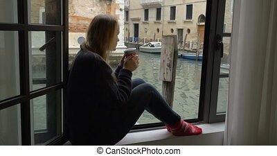 Woman with tea enjoying scene from the window - Steadicam...