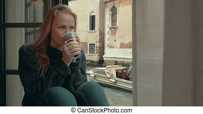 Wistful woman having coffee at home in Venice - Steadicam...