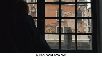 Woman opening window and enjoying Venice scenes - Steadicam...