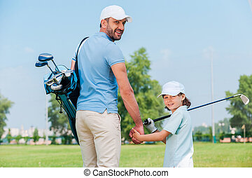 They are the big golf fans Happy young man and his son...