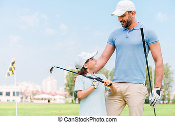 Little golfer with father. Happy young man and his son...
