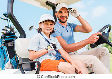 Two smiling golfers Happy young man and his little son...