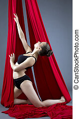 Shot of cute female dancer posing on aerial silks - Shot of...