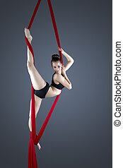 Flexible female gymnast performing aerial exercise, on grey...