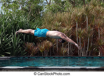 Man dive in blue swimming pool