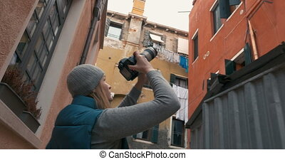 Female photographer taking pictures of old houses