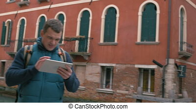 Tourist in Venice chatting on tablet PC - Steadicam shot of...