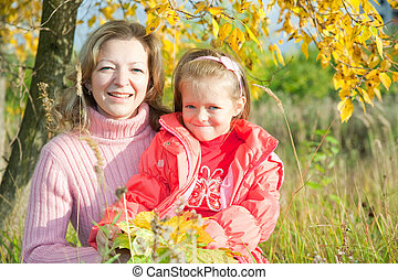 Woman with  little girl in autumn