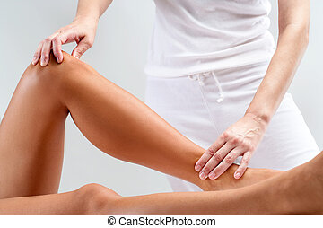 Osteopathic massage on female legs. - Close up of therapist...