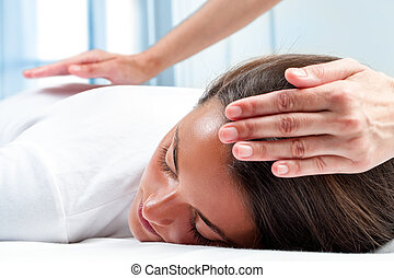 Therapists hands doing reiki therapy on girl. One hand on...