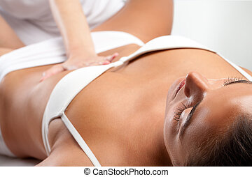 Woman at osteopathic massage with therapist hand on stomach.