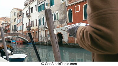Girl using tablet PC during the walk in Venice - Steadicam...