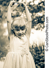 little girl with rised hands - little blond girl dancing...