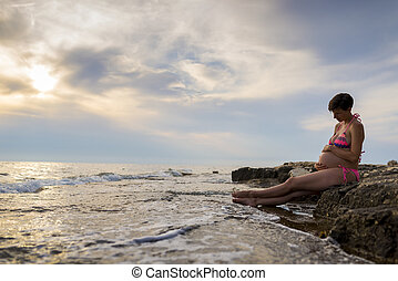 Pregnant woman in ninth month of pregnancy sitting on a rock...