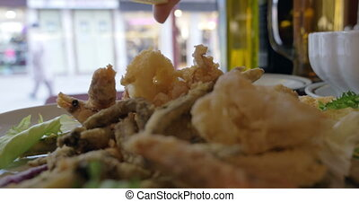 Squeezing the Lemon Wedge on Seafood - A close-up shot of a...