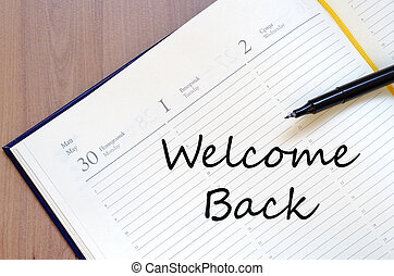 Welcome back text concept - Yellow blank notepad on office...