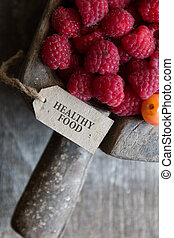 healthy food, raspberries and a tag with the inscription