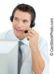 Smiling businessman with headset on working at a computer