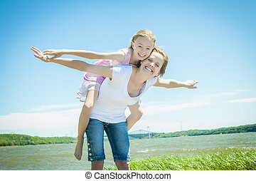 Young girl hugging her mother piggyback style - A Young girl...