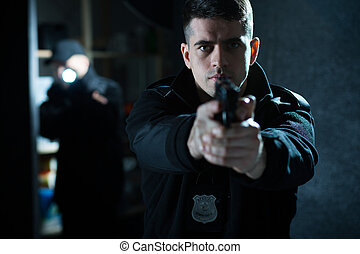 Policeman holding a handgun - Image of a confident handsome...