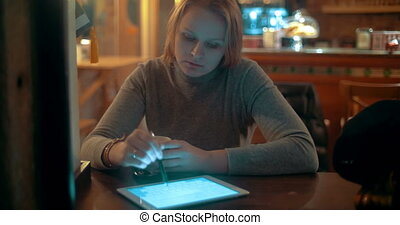 Woman Using Tablet PC with Stylus in Cafe - Young woman is...