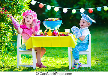Garden grill party for kids - Children grilling meat Family...