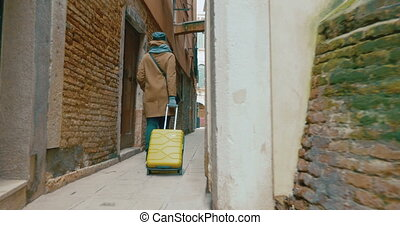 Woman with trolley back walking along the alleyway -...