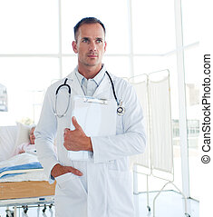 Serious doctor holding a medical clipboard in the hospital