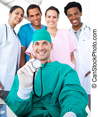 Smiling surgeon holding a stethoscope with his team in the background. Medical concept.