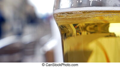 Glass with light beer in outdoor cafe - Close-up shot of a...