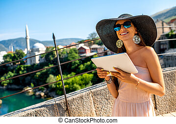 Female tourist using digital tablet in Mostar city - Young...