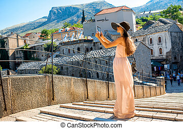 Woman photographing city view in Mostar - Female tourist...