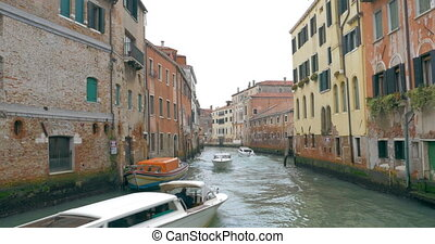 Motor boats sailing on canal in Venice - View to the narrow...
