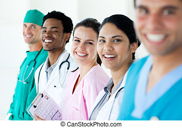 Smiling medical team in a line isolated on a white...