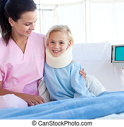 Smiling patient with a neck brace and her nurse in a...
