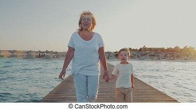 Grandmother and grandson having outdoor walk on resort -...