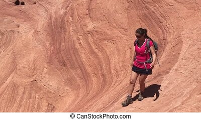 Girl hiker walking down wavy sandstone Horizontal...