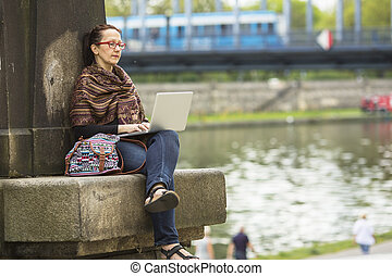 woman with laptop outdoors. - Young woman with laptop...