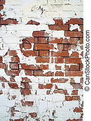 White paint peeling off a red brick wall.
