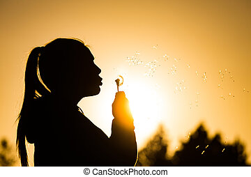 summer days - teenage girl backlit by the sun blowing a...